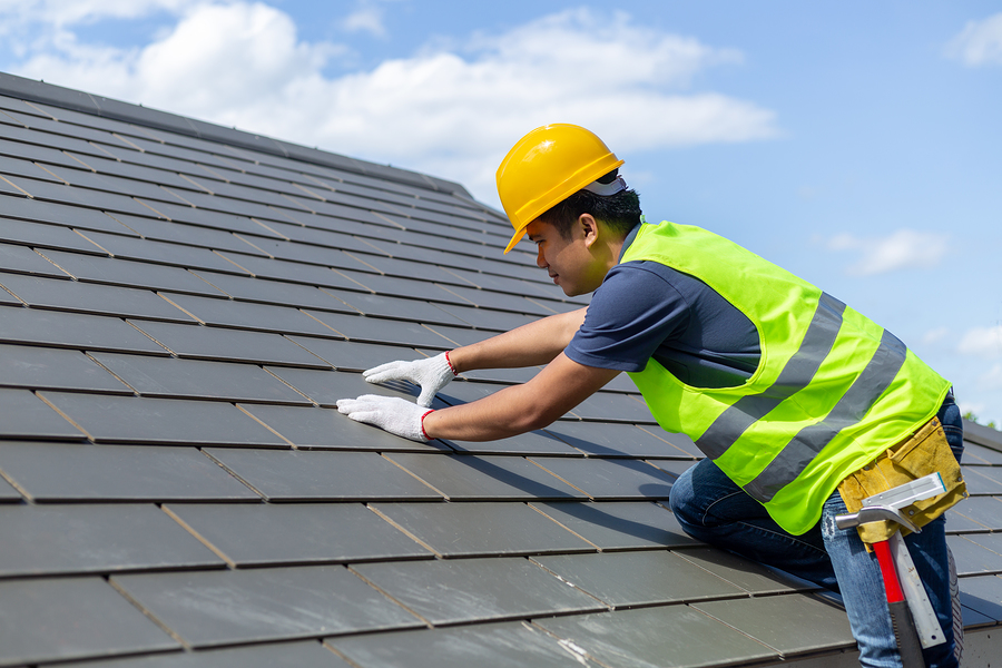 worker with white gloves replacing gray tiles or shingles on house with blue sky as background and copy space