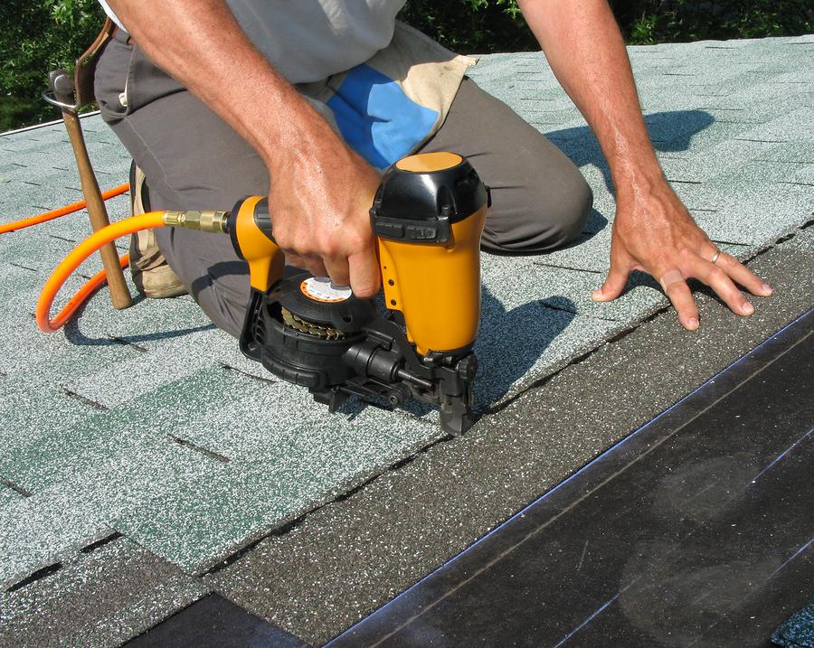 carpenter uses nail gun to attach asphalt shingles to roof