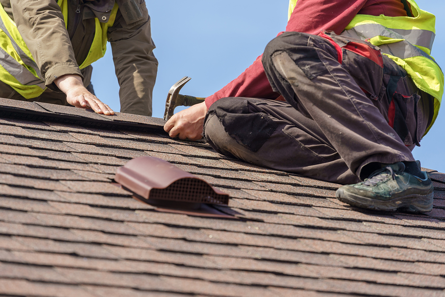 two mature roofers in protective uniform using helmet and installing asphalt shingle or roof tile on top of new house against blue sky