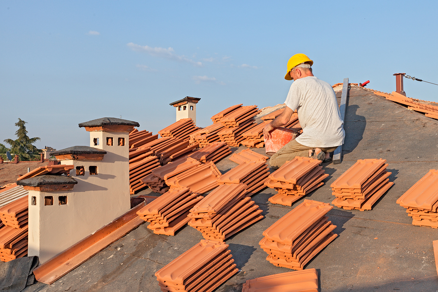 construction worker on a roof covering it with tiles