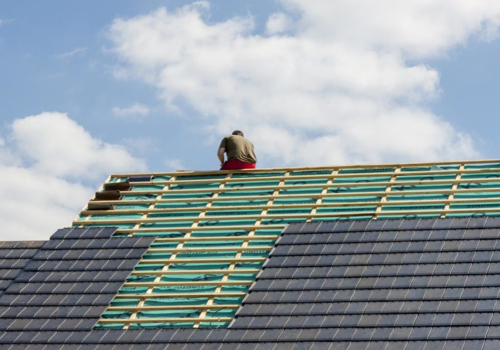 a man on the roof installing tile roof